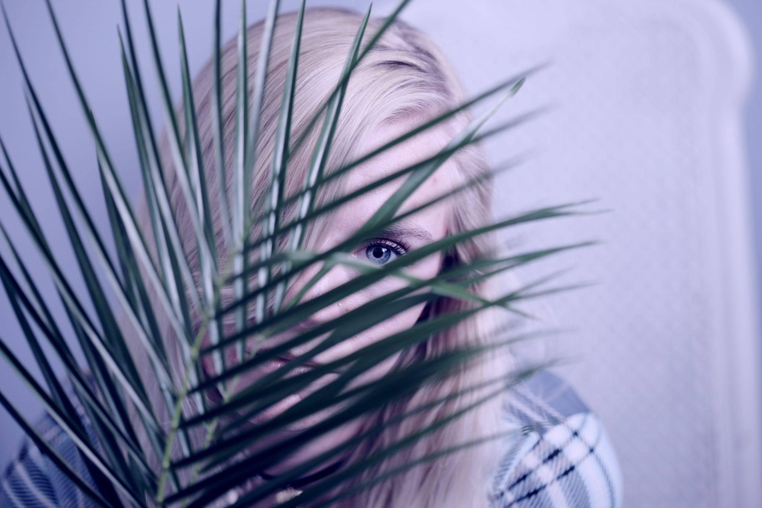 fată timidă se ascunde după o plantă