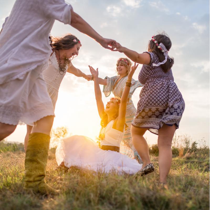 Femei dansand in iarba la apusul soarelui